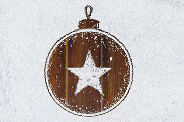 christmas card or new year background made of decorative ball symbol handwritten on snow and wooden table