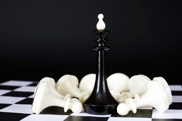 Chess king among defeated pawns. Total victory. Concept with chess pieces against black background