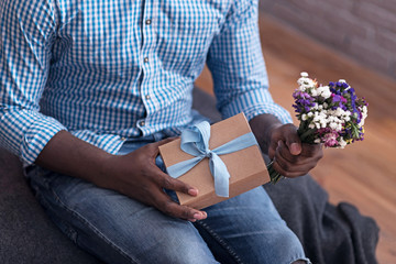 Close up of delighted man holding flowers and gift