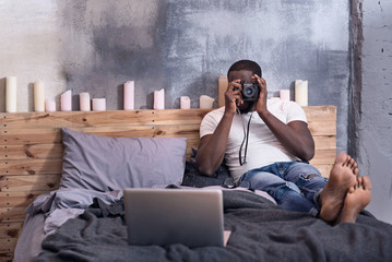 African man holding a camera in bedroom