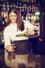 Composite image of pretty bartender pouring whiskey in glass