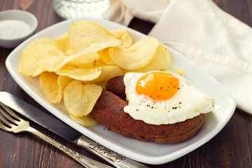 fried portuguese sausage alheira with egg and potato chips on white dish