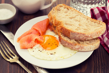 fried egg with smoked salmon and bread on white plate