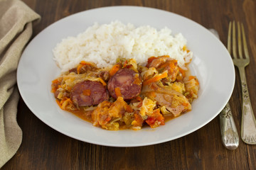 meat with cabbage,  beans and rice on white dish