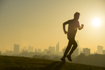 Silhouette of jogger running on the green grass of Primrose Hill in front of the misty London city skyline