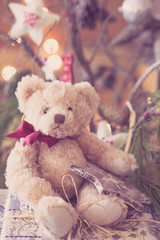 Christmas teddy bear with red scarf sitting alone over the Christmas gift