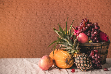 Many fruits on tablecloth.