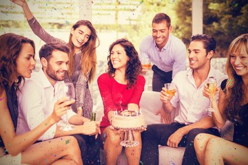 Composite image of woman celebrating her birthday with friends