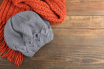 Knitted hat and scarf on wooden background