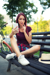 Red-haired girl sitting on the bench make selfie