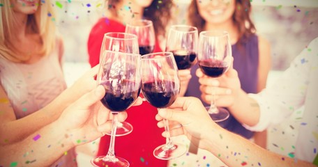 Composite image of cropped image of hand toasting wine glasses