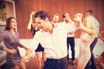 Composite image of cheerful friends dancing in party