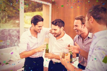 Composite image of men having drinks while standing together