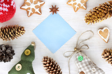 decorations for Christmas and New Year/ flat layout of the blue sheet for inscriptions surrounded by trees, cones and holiday cookies top view
