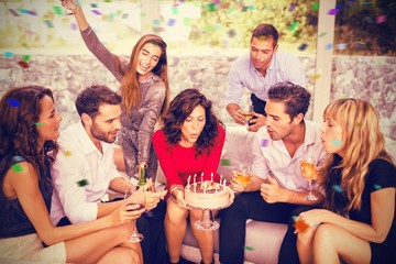 Composite image of woman blowing birthday candles with friends