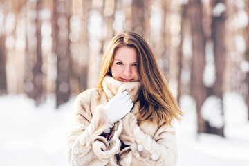 Winter portrait of young beautiful woman wearing fur coat. Snow winter beauty fashion concept.