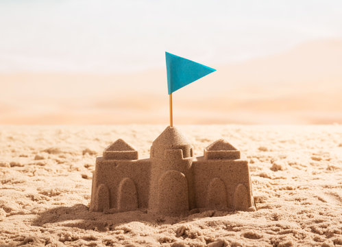 Sand castle with flag on the sea shore.
