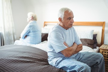 Sad senior couple sitting on bed
