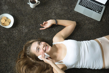 Top view portrait of a young attractive smiling woman in underwear lying on the carpet, talking on her phone, laptop near. Business, education concept photo, lifestyle