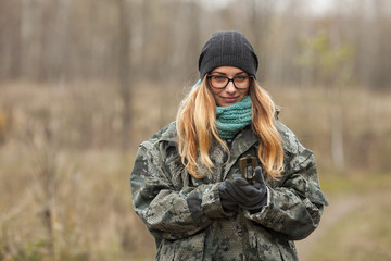 Young beautiful woman in camouflage outfit discovering nature in the forest with compass. Travel lifestyle concept.