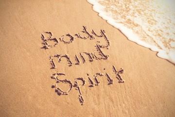 Body mind spirit text written on sand with surf
