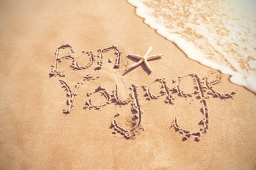 Bon voyage written on sand