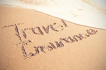 Travel Insurance text written on sand