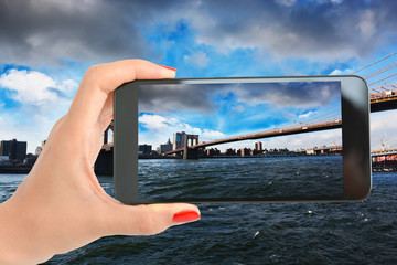 View over Brooklyn Bridge, New York with woman hand taking a picture with smartphone