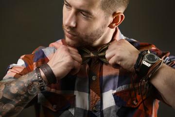 Young tattooed man posing on dark background