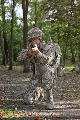 Soldier taking aim from rifle in forest
