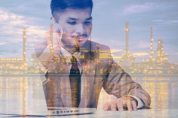 Double exposure of businessman using smartphone and laptop with  oil refinery At sunset for business concept