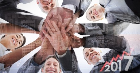 Composite image of business team standing hands together