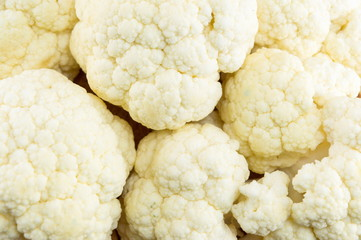 Raw cauliflower on a pile forming background