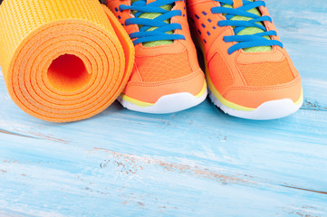Sport equipment and sneakers. Yoga mat and sport shoes on blue wooden background. Concept healthy lifestyle, healthy food, sport and diet. Copy space