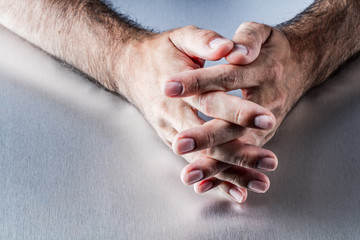 anonymous male hairy hands crossing fingers together waiting or thinking