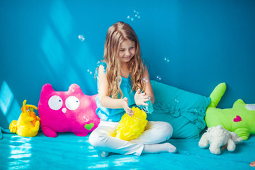 little cute girl playing with bubbles on blue blanket