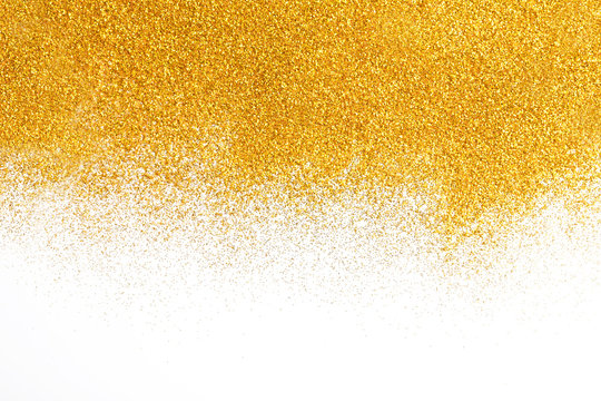 Golden glitter sand texture on white, abstract background.