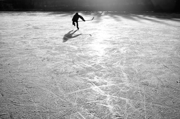 hockey player on the ice on sunset - black and white photo