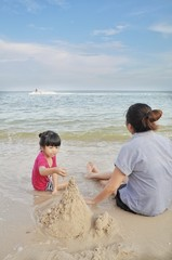 Mother and her daughter made a sand castle with a beautiful sea background.