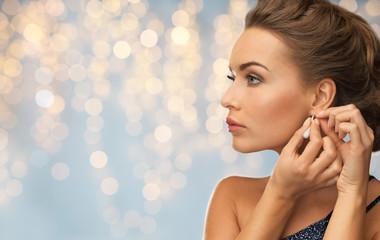 close up of woman woman fastening diamond earring