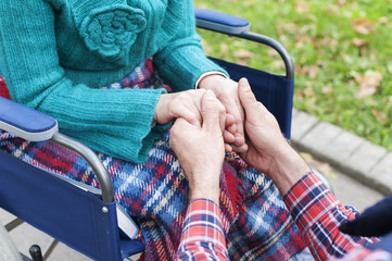 Close up of male hand holding the hand of a woman who sits in a wheelchair, support