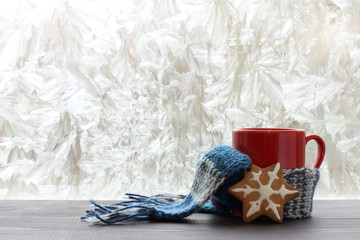 warming holiday mood/ red mug with a warm scarf and pastries in the background of a winter window