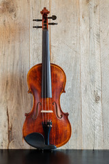 Wooden Classic Violin on a Black Surface with Weathered Wood Background