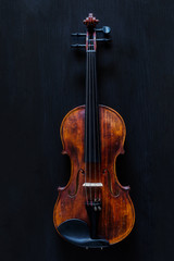 Wooden Vintage Classic Violin on a Black Textured Surface