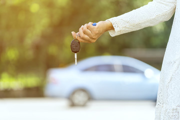 Young woman holding her new car key at Outdoor parking