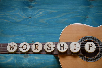 guitar on teal wooden background with wood pieces on it lettering the word: WORSHIP