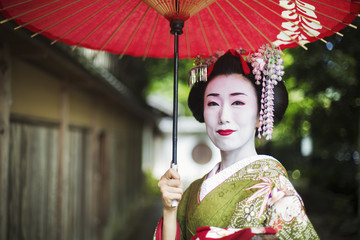A woman dressed in the traditional geisha style, wearing a kimono and obi, with an elaborate hairstyle and floral hair clips, with white face makeup with bright red lips and dark eyes holding a red paper parasol.