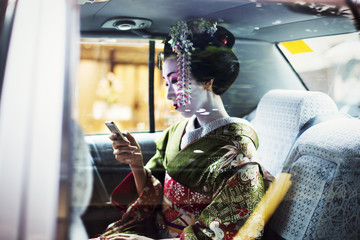 A woman dressed in the traditional geisha style, wearing a kimono and obi, with an elaborate hairstyle and floral hair clips, with white face makeup with bright red lips and dark eyes in a car using a smart phone.