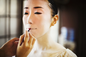 A modern woman creating the traditional geisha vivid red lips by painting on lipstick with a fine brush. White face makeup.