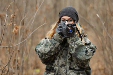 Young beautiful woman in camouflage outfit discovering nature in the forest with photo camera. Travel photography lifestyle concept.